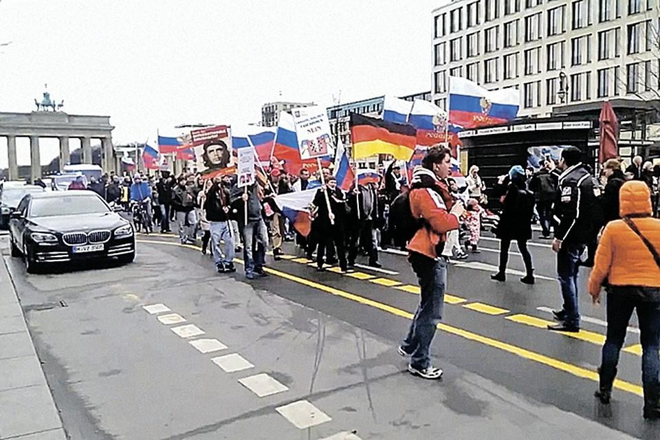 Немцы прошли с российскими флагами от Бранденбургских ворот маршем против очернения Москвы.