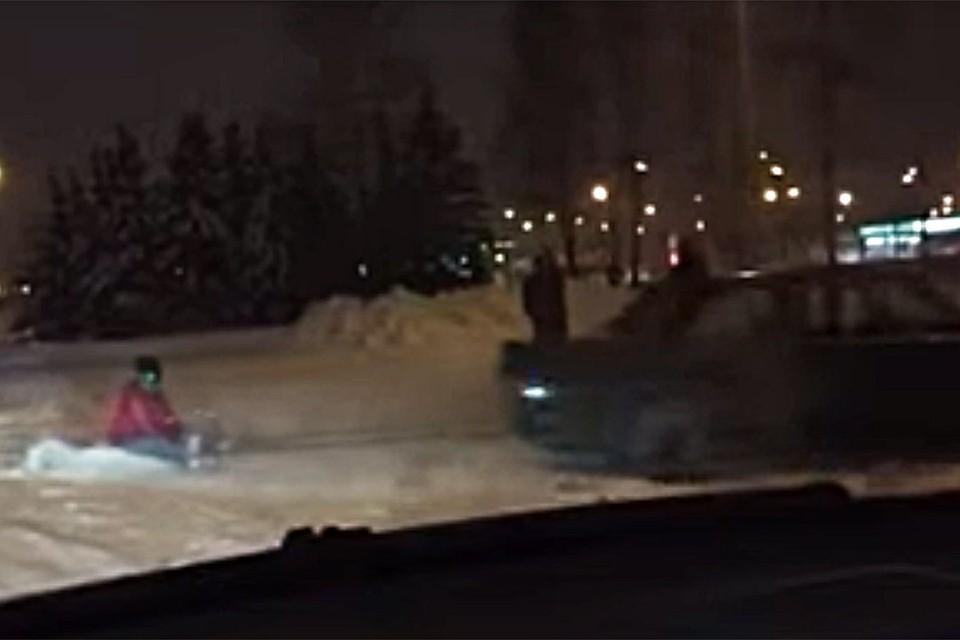 На видео водитель БМВ лихо рассекает с привязанными санками, на которых сидит мальчик лет 12. Фото: кадр с видео Тимофея Дранчука.