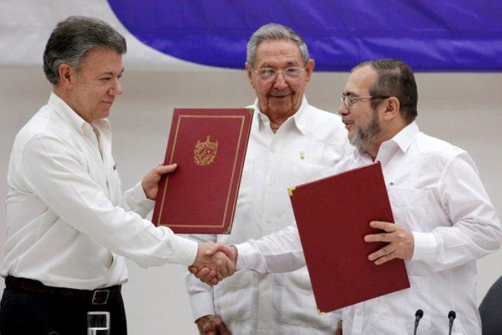 Исторический момент: президент Колумбии Мануэль Сантос (слева) и лидер повстанцев ФАРК Родриго Лондоно (справа) пожали друг другу руки в присутствии Рауля Кастро