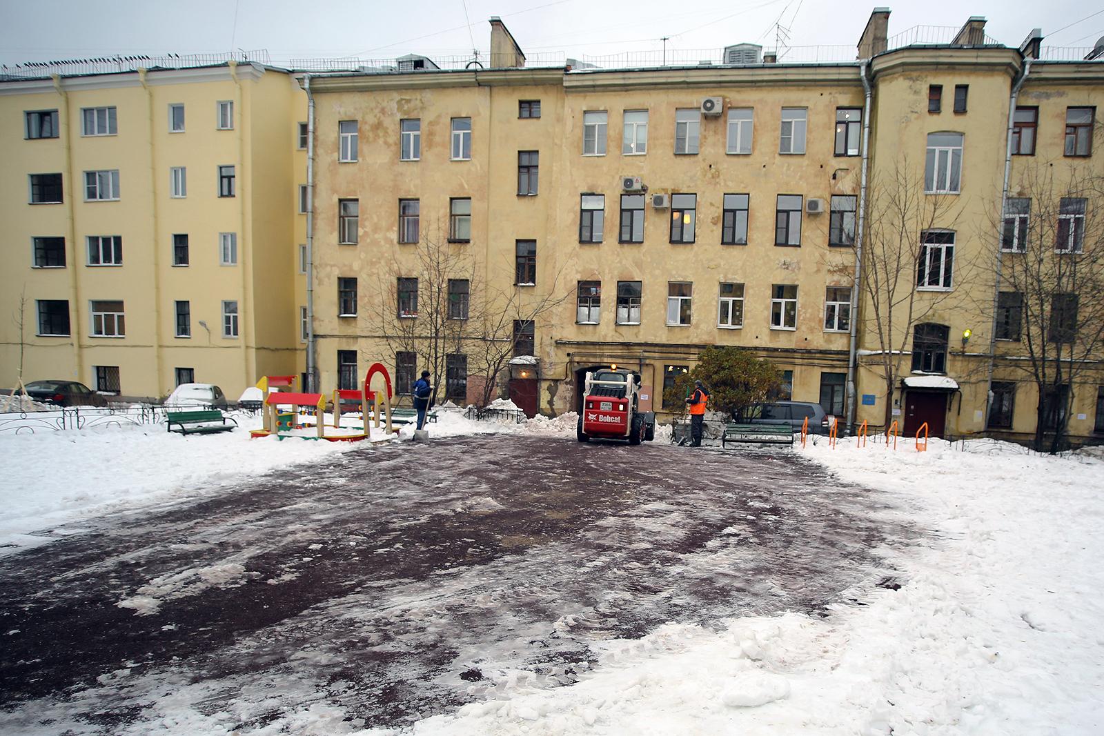 Во дворе, где произошла трагедия, рабочие убирают следы взрыва.