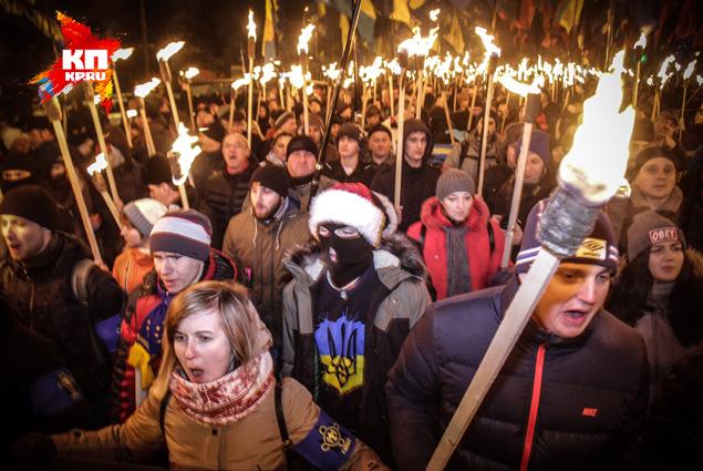 В руках у людей – красно-черные флаги и горящие факелы. Фото: Олег ТЕРЕЩЕНКО