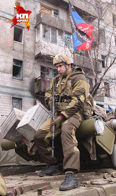 Ополченец ДНР возле девятиэтажки, которая  в последнее время превратилась в пресс-центр. Фото: Александр КОЦ, Дмитрий СТЕШИН