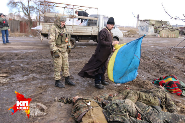 Батюшка поднимает украинский флаг, аккуратно сматывает его. Фото: Александр КОЦ, Дмитрий СТЕШИН