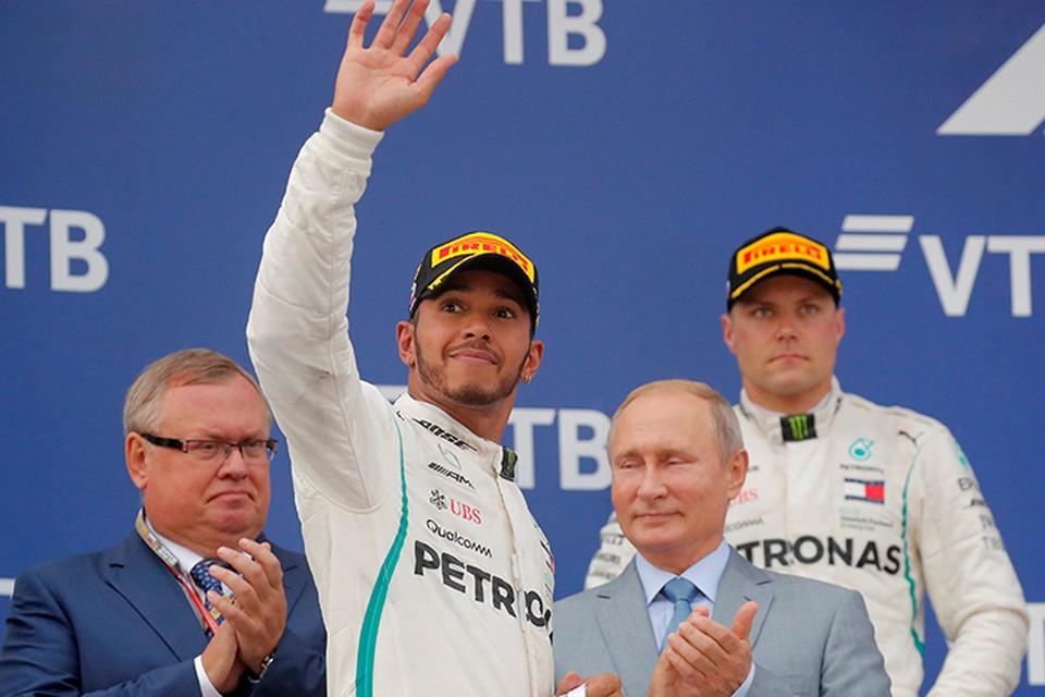 Президент России вручил англичанину кубок победителя и покинул подиум, чтобы не попасть под душ из шампанского