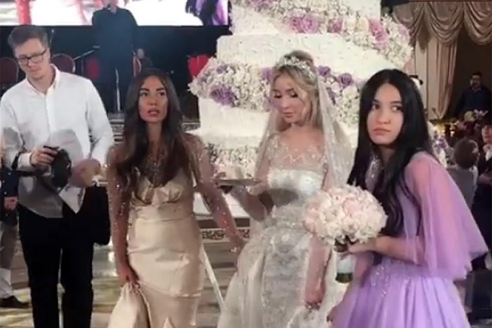 Скромная невеста Айна в платье примерно за 15 миллионов рублей на фоне двухметрового торта где-то за 500 тысяч
