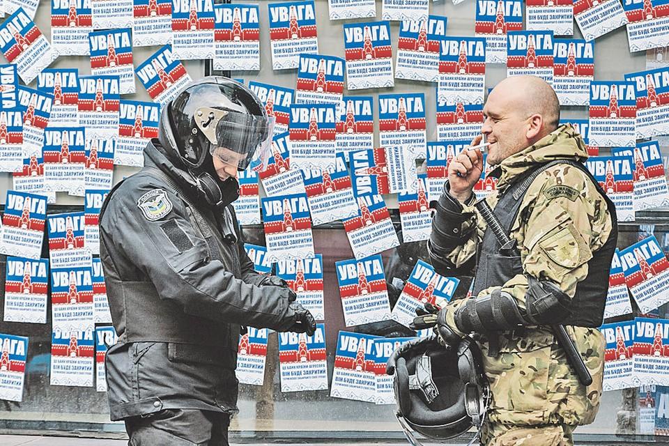 Военный и полицейский охраняют порядок у филиала Сбербанка в Харькове, который националисты облепили листовками «Банк агрессора». Но листовки не снимают... Фото: РИА Новости