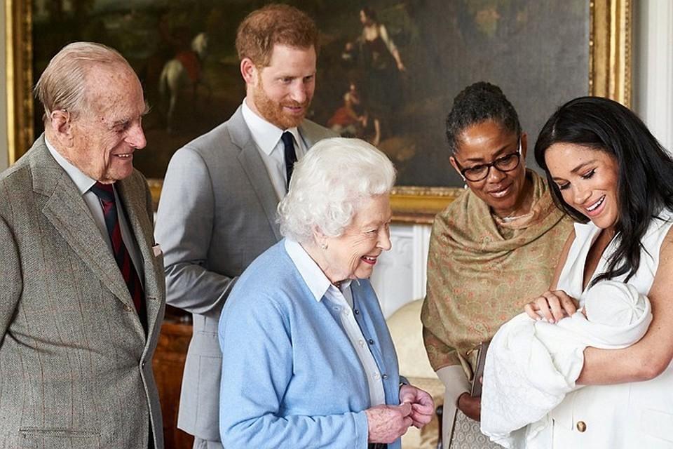 По фото видно, что Елизавета II и ее муж герцог Эдинбургский расплываются в улыбке, глядя на ребенка