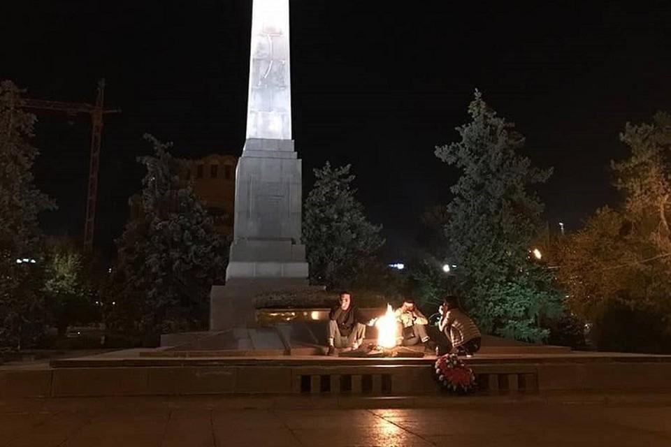 Молодые люди расположились на плитах возле Вечного огня.