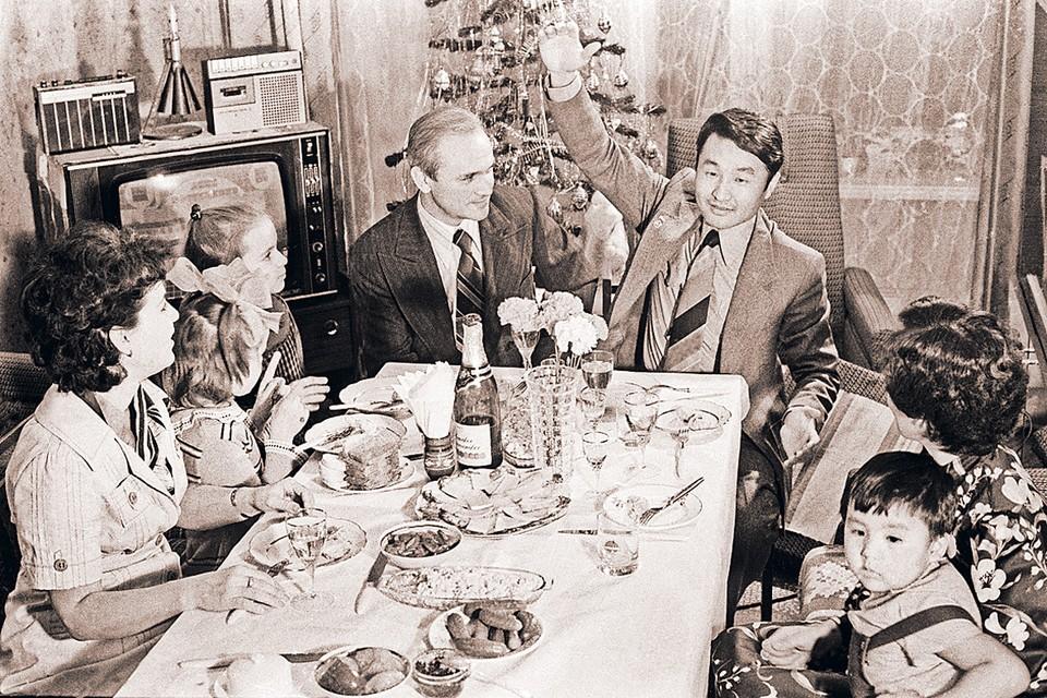Космонавты международного экипажа корабля «Союз-39» Владимир Джанибеков (слева) и Жугдэрдэмидийн Гуррагча из Монголии (справа) со своими семьями встречают Новый, 1981 год. Снимок, конечно, постановочный. Но это типичное советское застолье. Разве что разносолов бывало и побольше. Фото: Альберт ПУШКАРЕВ/Архив/ТАСС