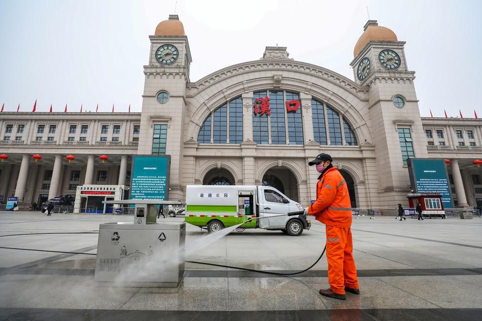 Рабочий дезинфицирует площадь перед вокзалом в Ухане.