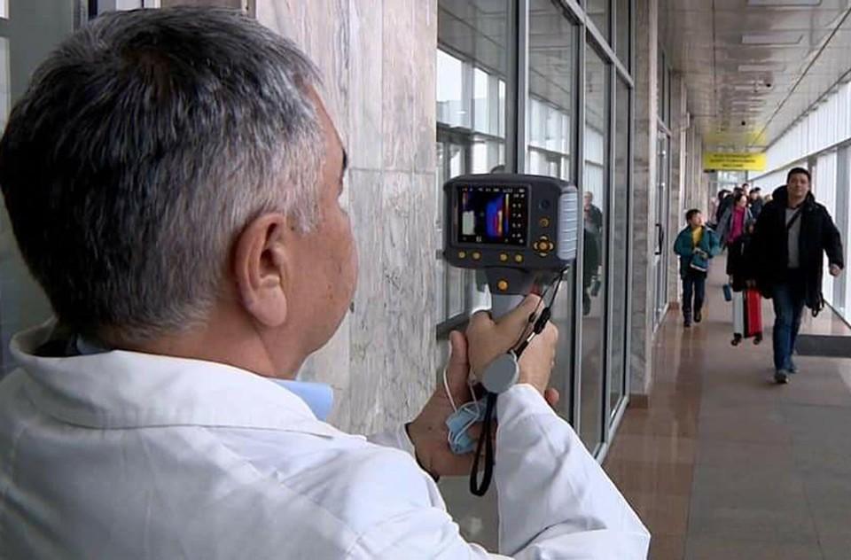 Медики с помощью тепловизоров проверяют прибывающих пассажиров.