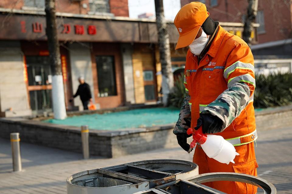 Дворник занят дезинфекцией мусорных контейнеров на опустевших улицах Пекина.