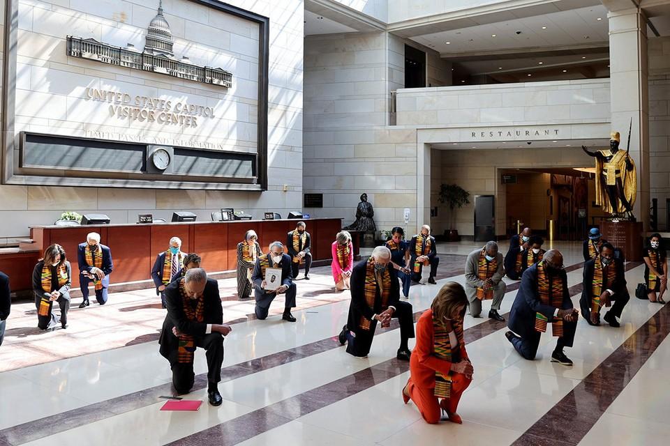 Американские сенаторы во время акции c преклонением колена в зале Капитолия в Вашингтоне.