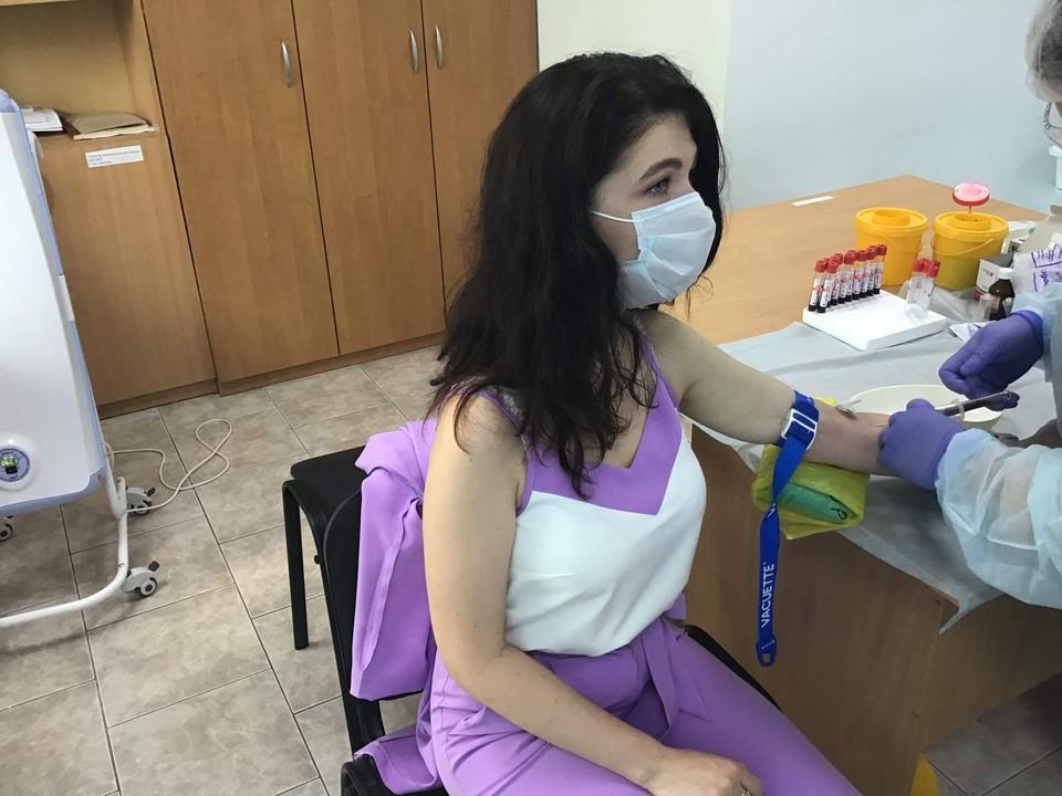 Девушка сдаёт тест на антитела к COVID-19
