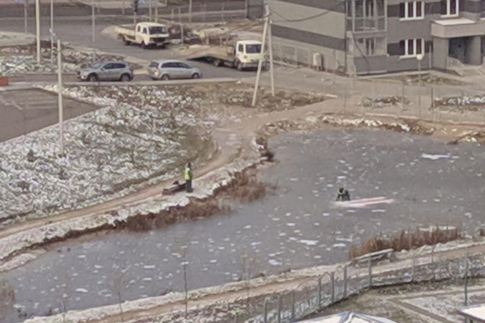 Коммунальщики в Минске рубили лед топором, чтобы достать БЧБ-флаг. Фото предоставлено читателем