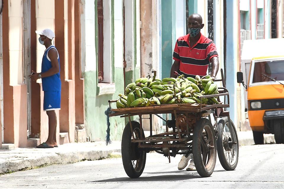 Продавец бананов катит свою тележку по улицам Гаваны, Куба.