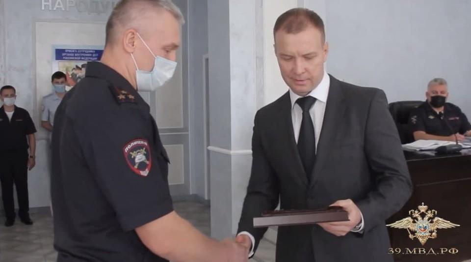 Игорь Илларионов вручает руководителю областной Госавтоинспекции Геннадию Бубенову наградной пистолет.