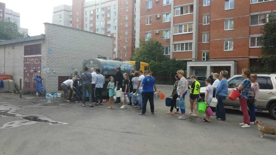На улице Урывского люди стоят в очереди за водой.
