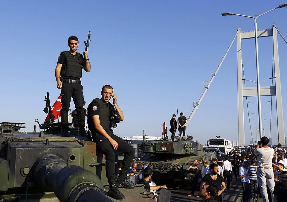 Полицейские стоят на броне танка, оставленного военными мятежниками на подступах к мосту через Босфор.