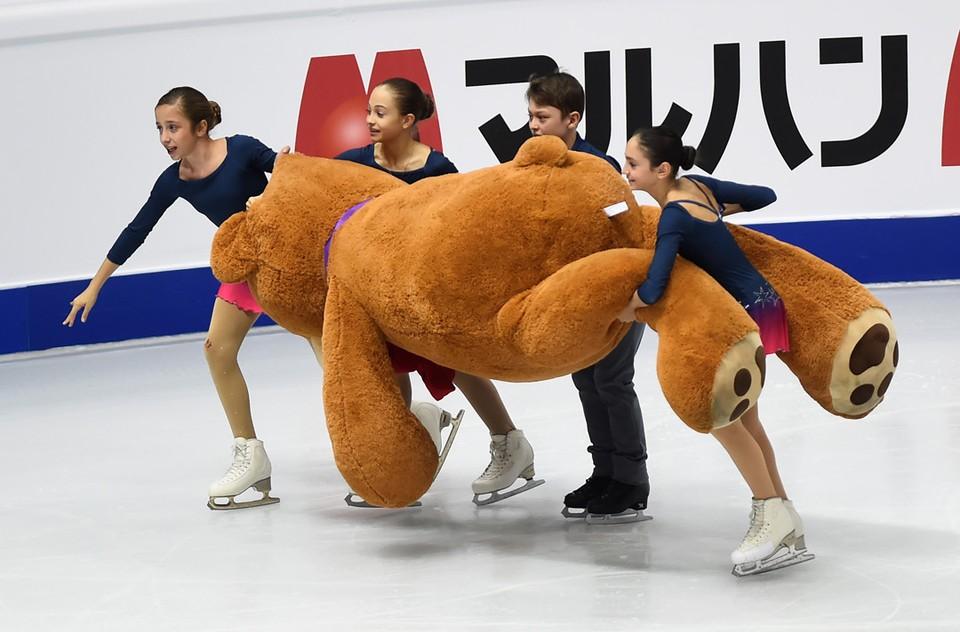 Волонтеры убирают со льда огромного игрушечного медведя, брошенного зрителями финала Гран-при по фигурному катанию в Турине.