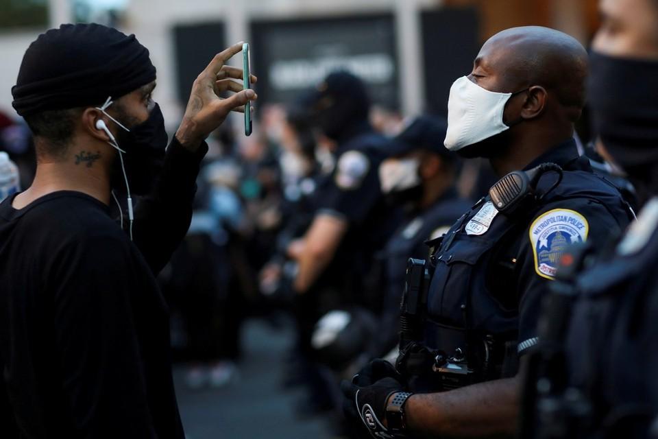 Участник уличных протестов в Вашингтоне общается с сотрудником полиции.