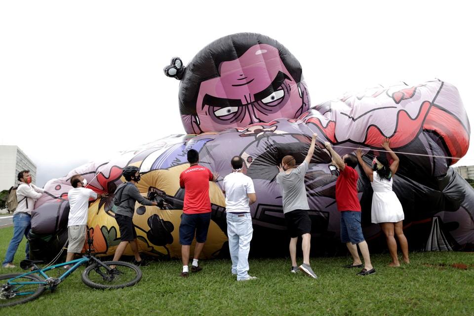 Фермеры надувают гигантскую фигуру президента Бразилии Жаира Балсонару перед началом протестной акции в Рио.
