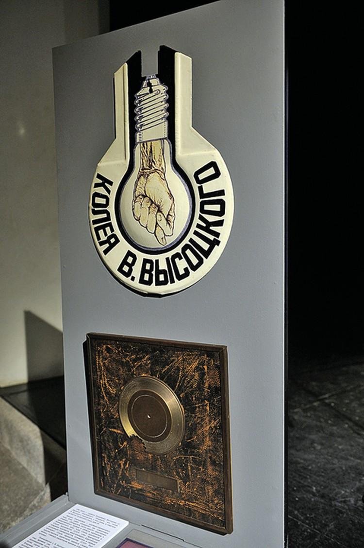 Номерной знак на дом «Колея Высоцкого» работы неизвестного художника и бронзовый диск с надписью: «Володе в счет всех золотых дисков его».