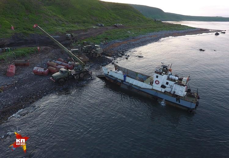 Техника на пляже в бухте Двойная подсыпает молы, чтобы плашкоут-транспортер с килекторного судна мог забирать грузы круглосуточно