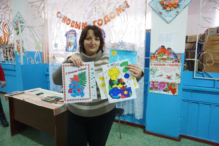Директор школы Самарская Оксана Викторовна показывает рисунки школьников.