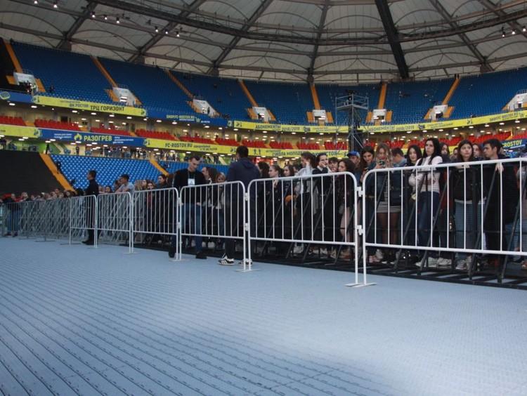 Серая плитка под ногами зрителей, стоящих на поле.