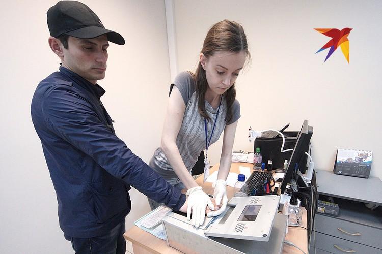 Екатеринбург. Сотрудница универсального миграционного центра проводит дактилоскопию рука иностранного гражданина во время оформления документов.
