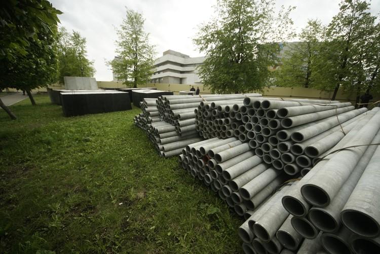 Внутри площадки экскаватор и полно бетонных блоков и труб