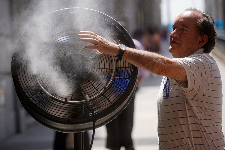 Мужчина охлаждается у уличного вентилятора в Мадриде.