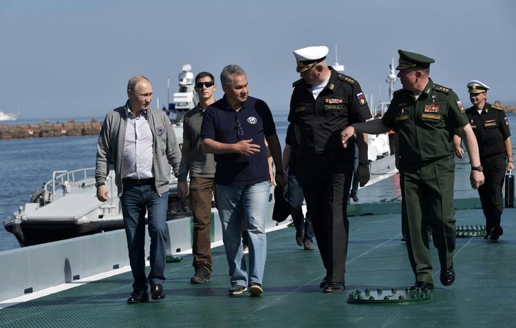 Путин в сопровождении министра обороны Сергея Шойгу прибыл на катере к плавучему причалу