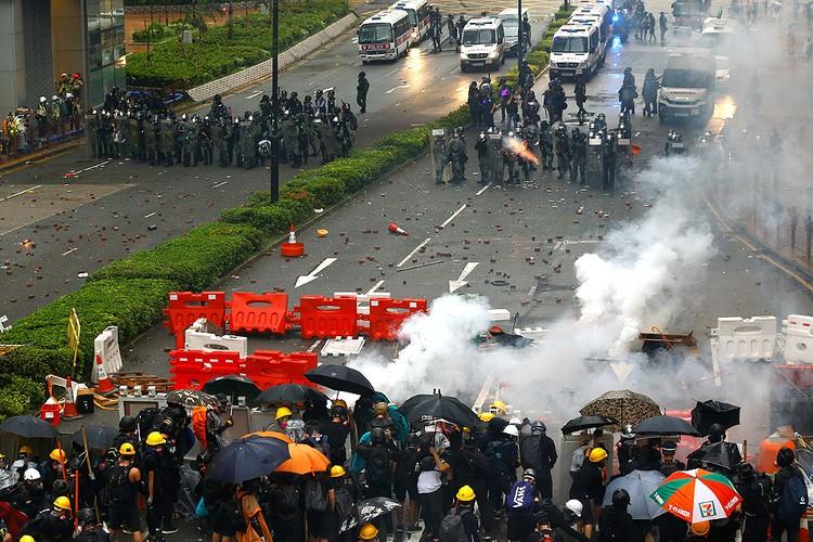"""Уличные баррикады в Гонконге. Время от времени дело доходит до """"рукопашных"""" стычек полицейских и протестующих."""