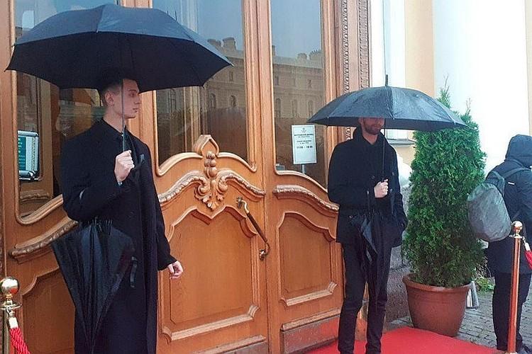 Перед Юсуповским дворцом гостей встречали крепкие мужчины с черными зонтами.