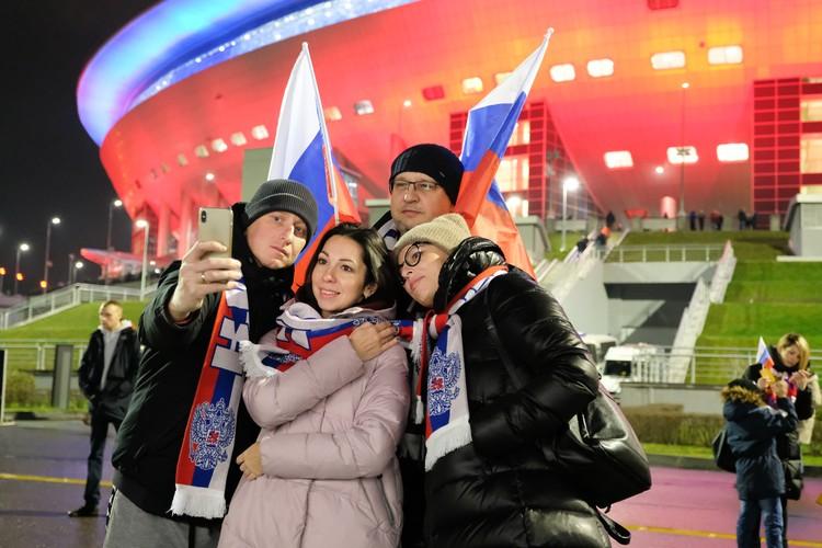 Фанаты радостные шли на матч и фотографировались на фоне пылающего красивой подсветкой стадиона