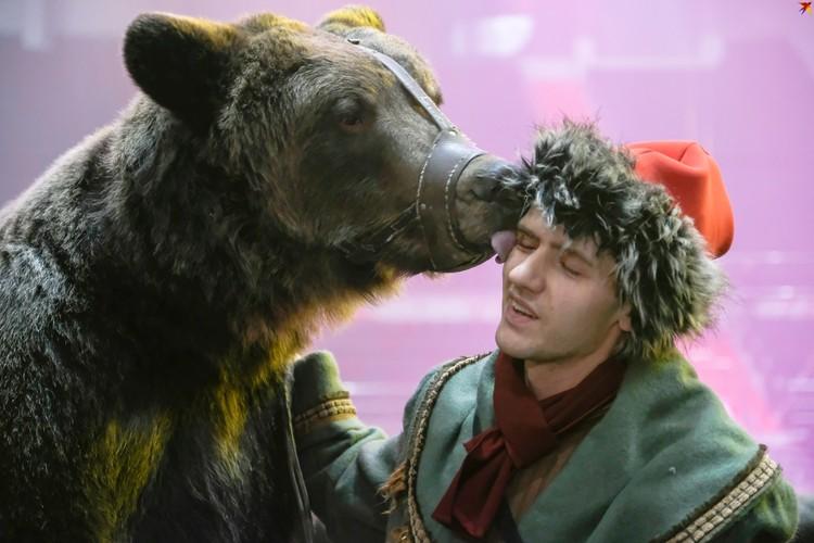 Бурый медведь Яков Потапыч целует своего дрессировщика.