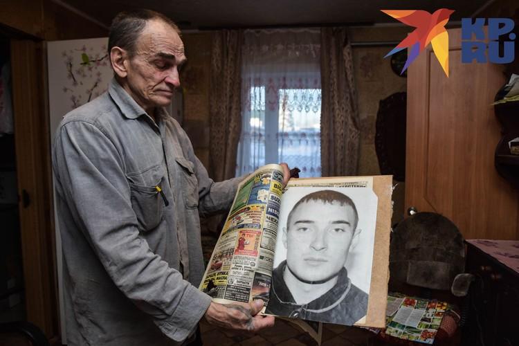 Сергей Александрович держит в руках фото сына.