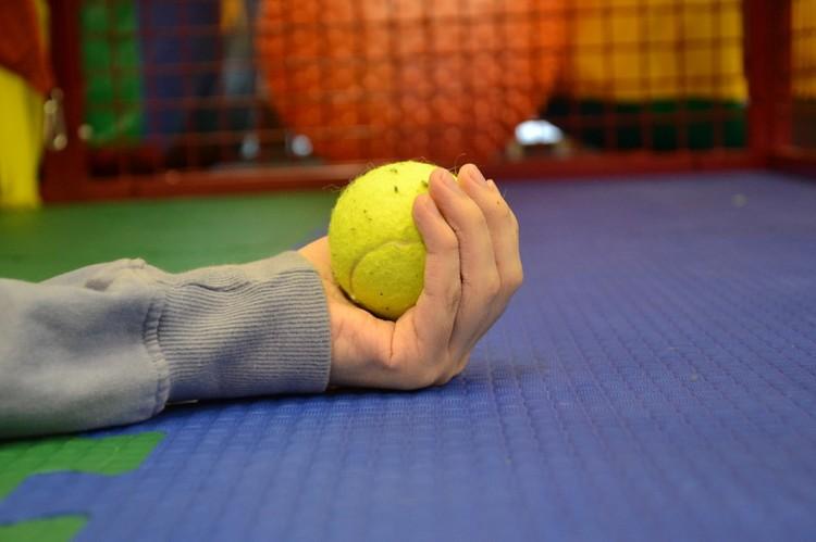 Мальчик лежит на спине с раскинутыми руками, в правой – ненавистный теннисный мячик Фото: предоставлено БЦ «Радуга»