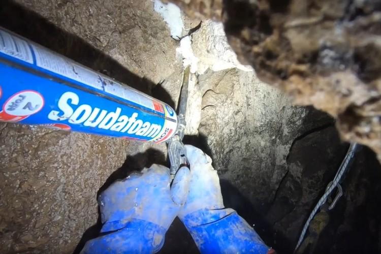 Ненадежные камни спелеологи крепят монтажной пеной. Фото: кадр видео Анатолия Пряшникова