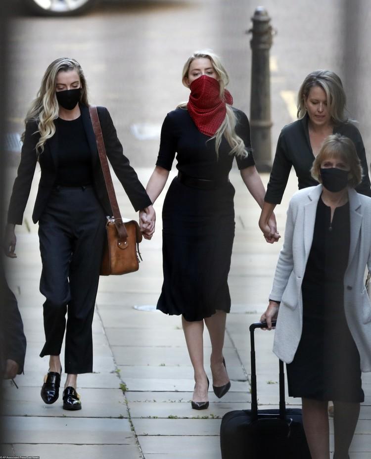 Эмбер (в центре) пришла в суд вместе с сестрой Уитни (слева) и адвокатами.