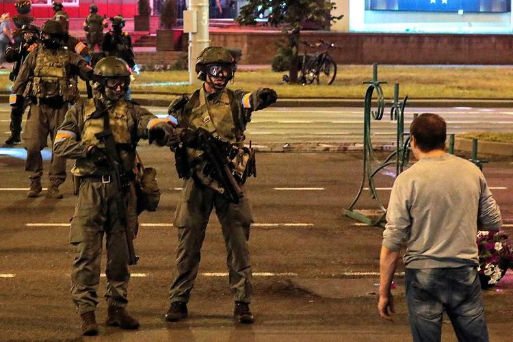 Бойцы внутренних войск пытаются отогнать протестующего.