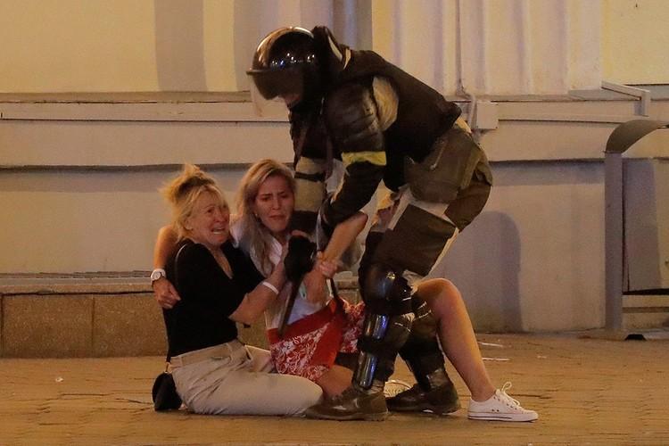 Сотрудник ОМОНа пытается выдворить с площади двух женщин, Минск, вечер 8 августа.
