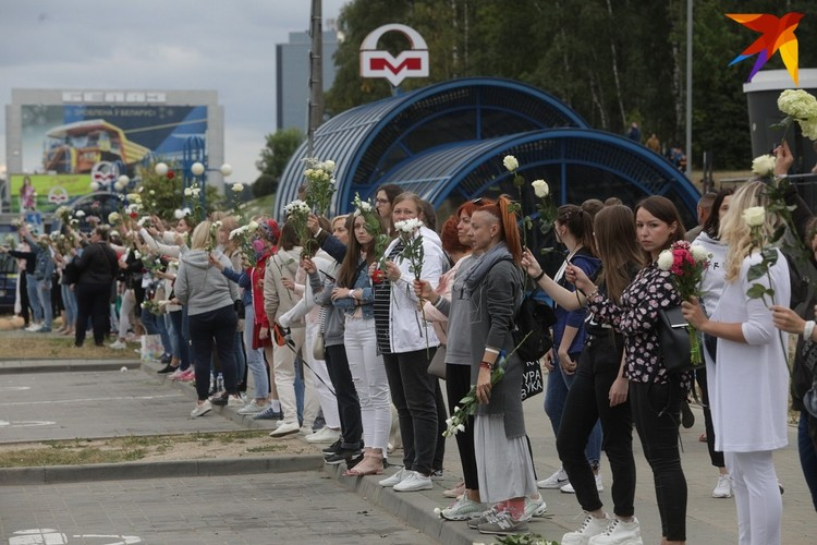 """Вечером женщины с цветами выстроились у станции метро """"Уручье""""."""