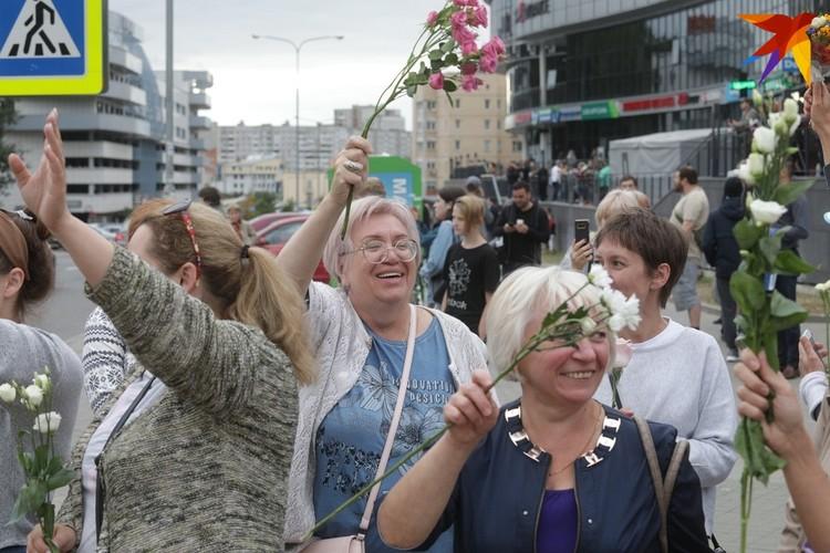 Женщины держат в руках цветы, как символ мира.