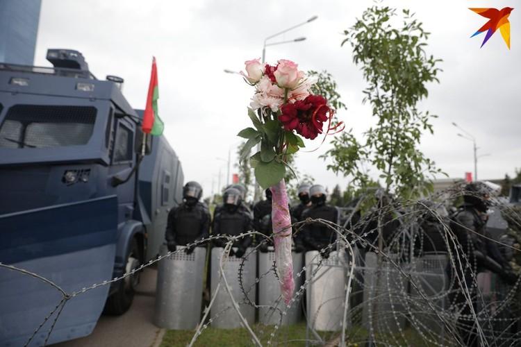 Протестующие оставляи цветы на колючих проволоках.