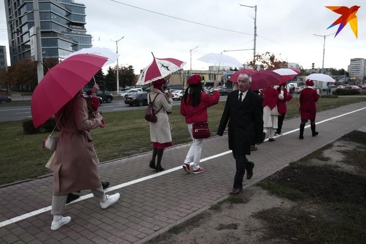 Девушки проходят мимо главного здания Белгазпромбанка
