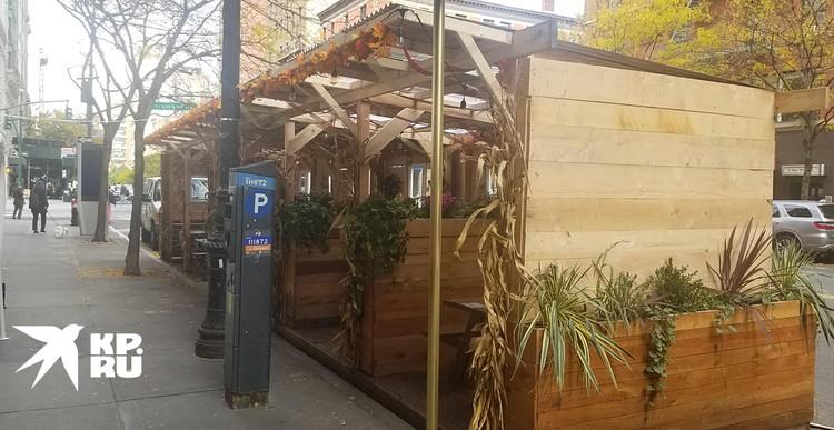 На каждом углу, прямо на проезжей части что-то похожее на деревянные сараи: согласно указу мэра, кафе и рестораны могут принимать посетителей только снаружи