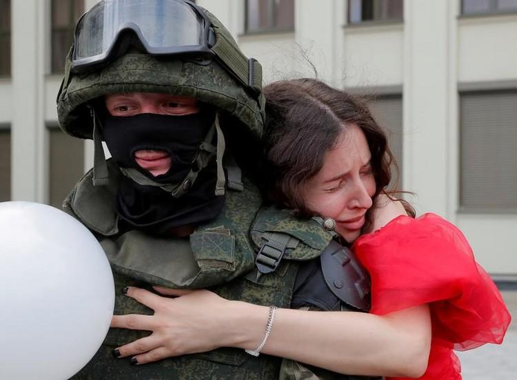 Участница протестов обнимает силовика из оцепления на акции 14 августа возле Дома правительства в Минске. Фото: Василий ФЕДОСЕНКО, REUTERS